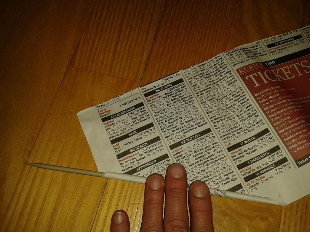 Aufrollen der Zeitung auf einer Stricknadel